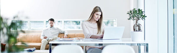 Vrouw zat aan een bureau op een laptop