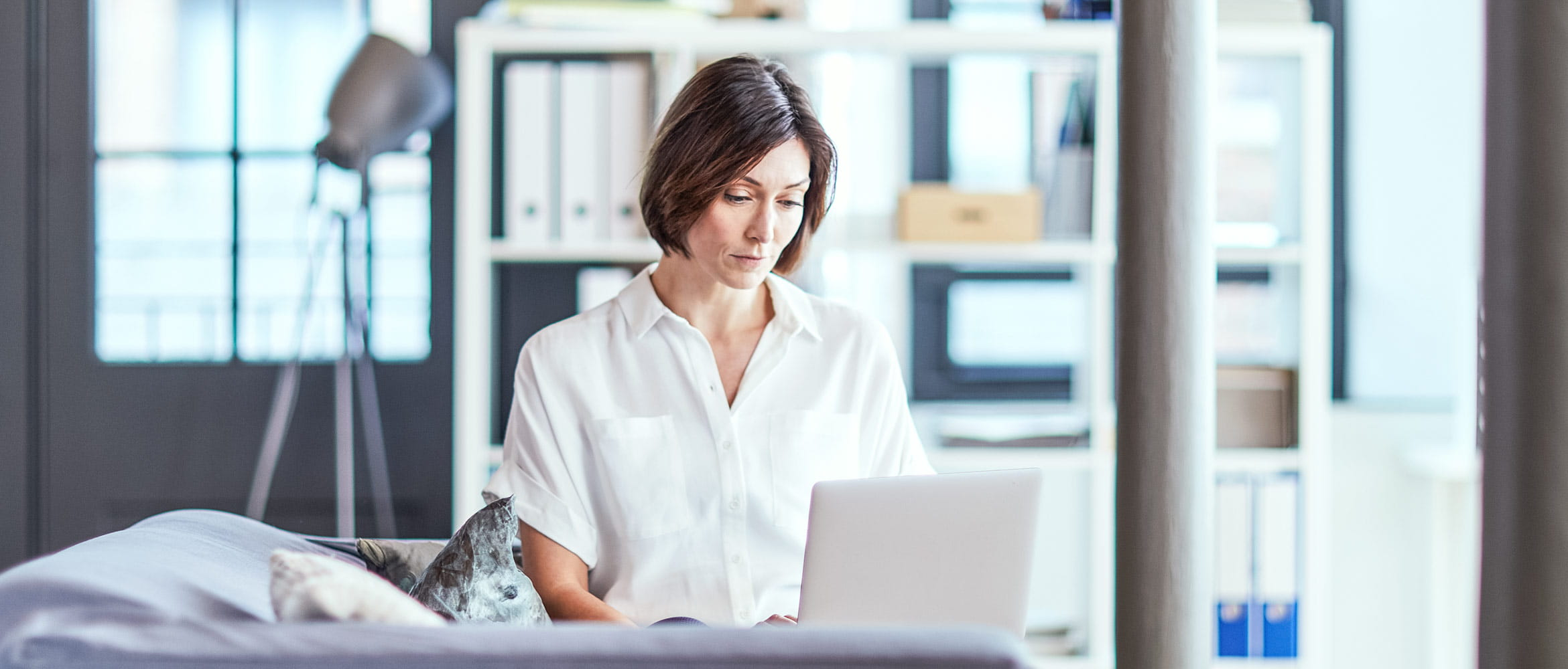 Woman sat at her desk typing on her laptop in office setting