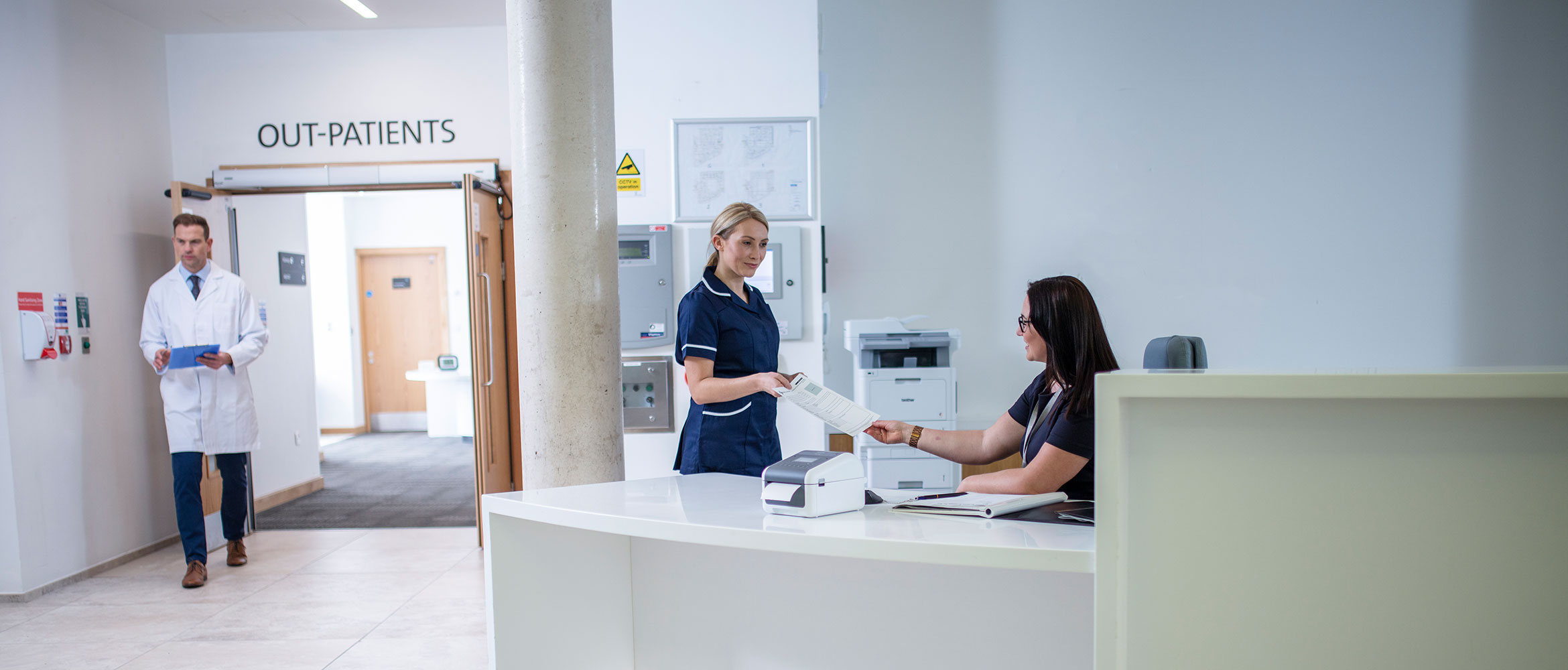 Receptionist wearing glasses sat at desk with nurse and doctor working in background