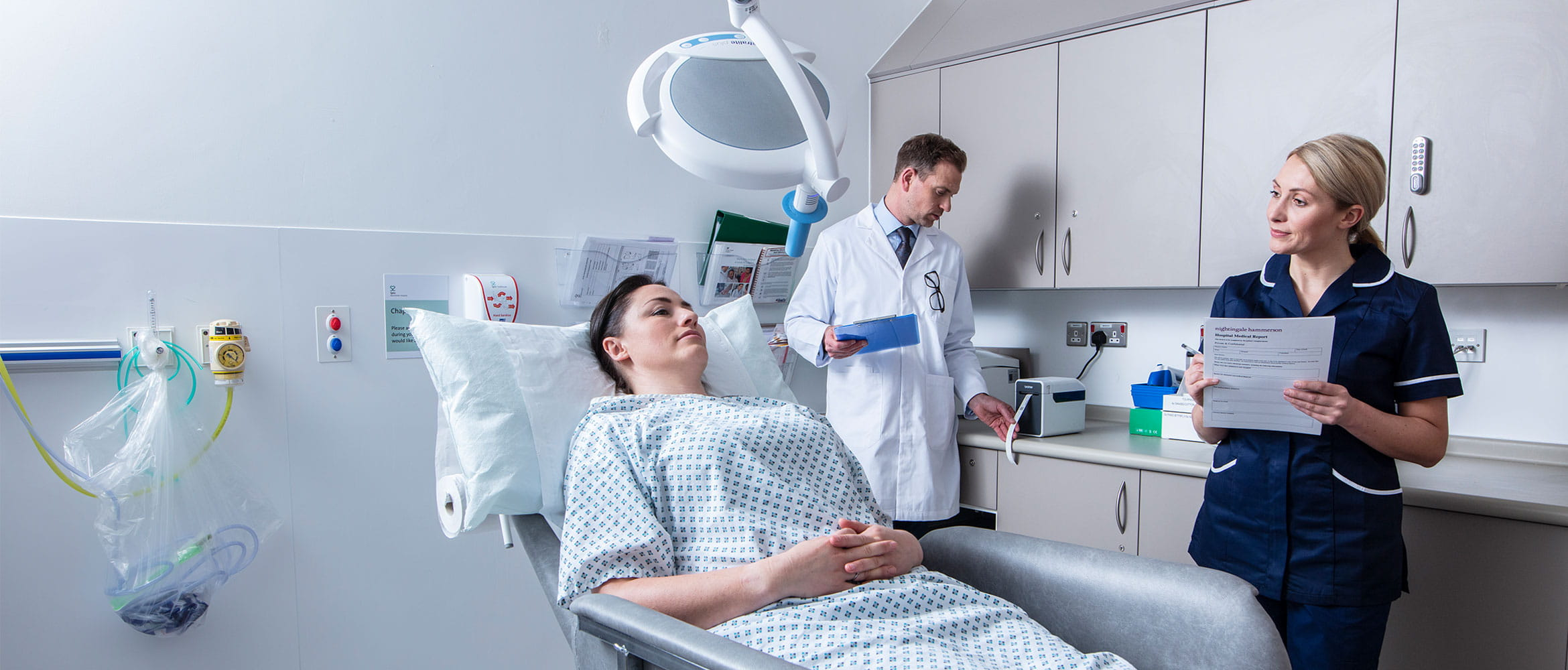 Female patient laid down in treatment room with male doctor in white coat stood at the back and female nurse stood with form