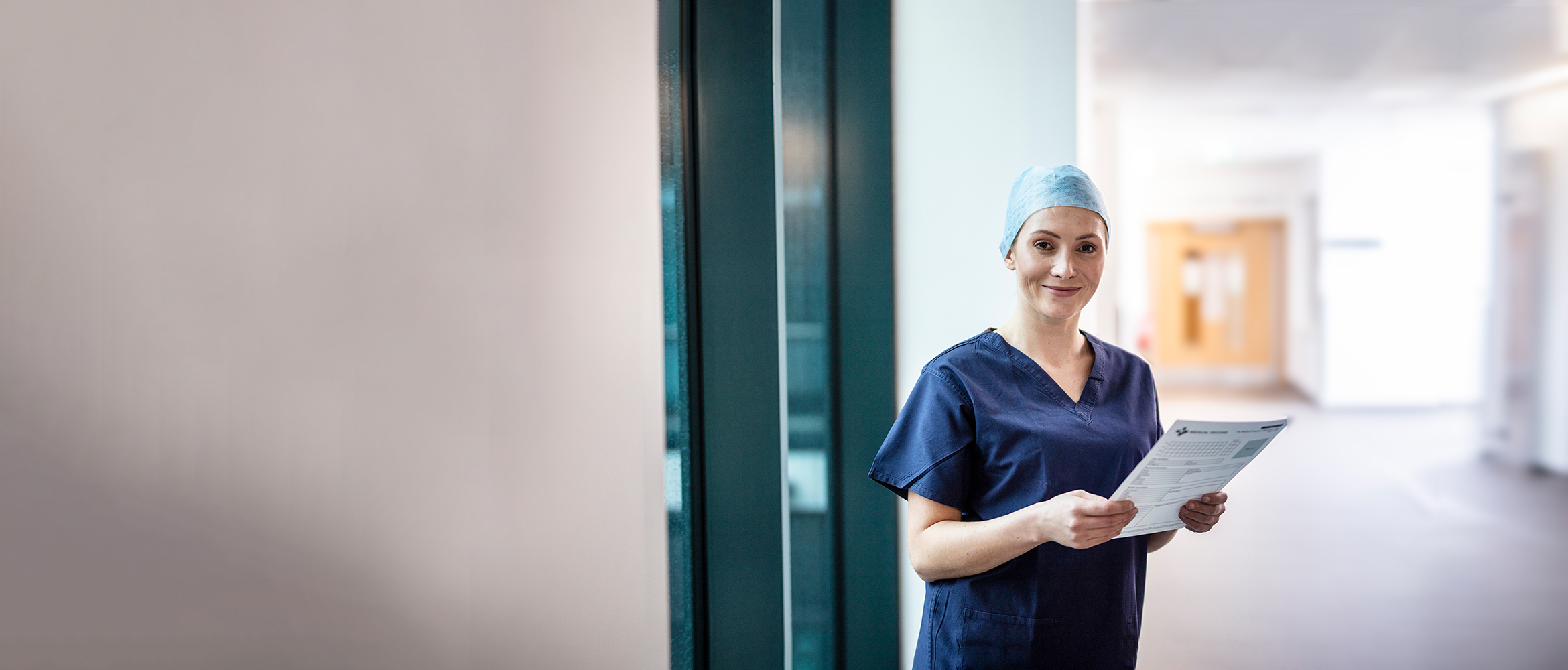 Female doctor wearing surgical scrubs and hat holding blue folder, in corridor with door in background