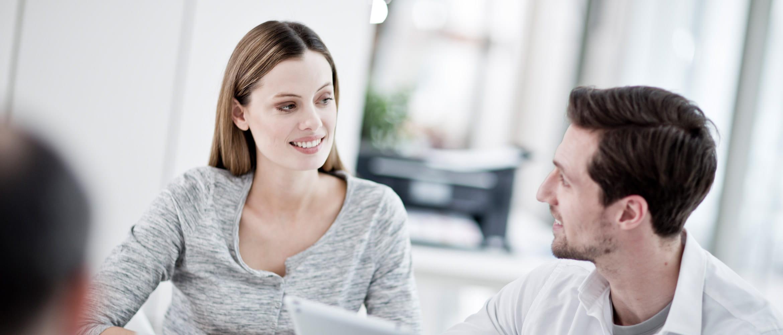 De man en de vrouwen voor laptop glimlachen, printer op de achtergrond