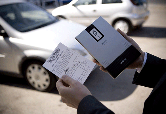 MW printer held in man's hand with A6 printed car rental form