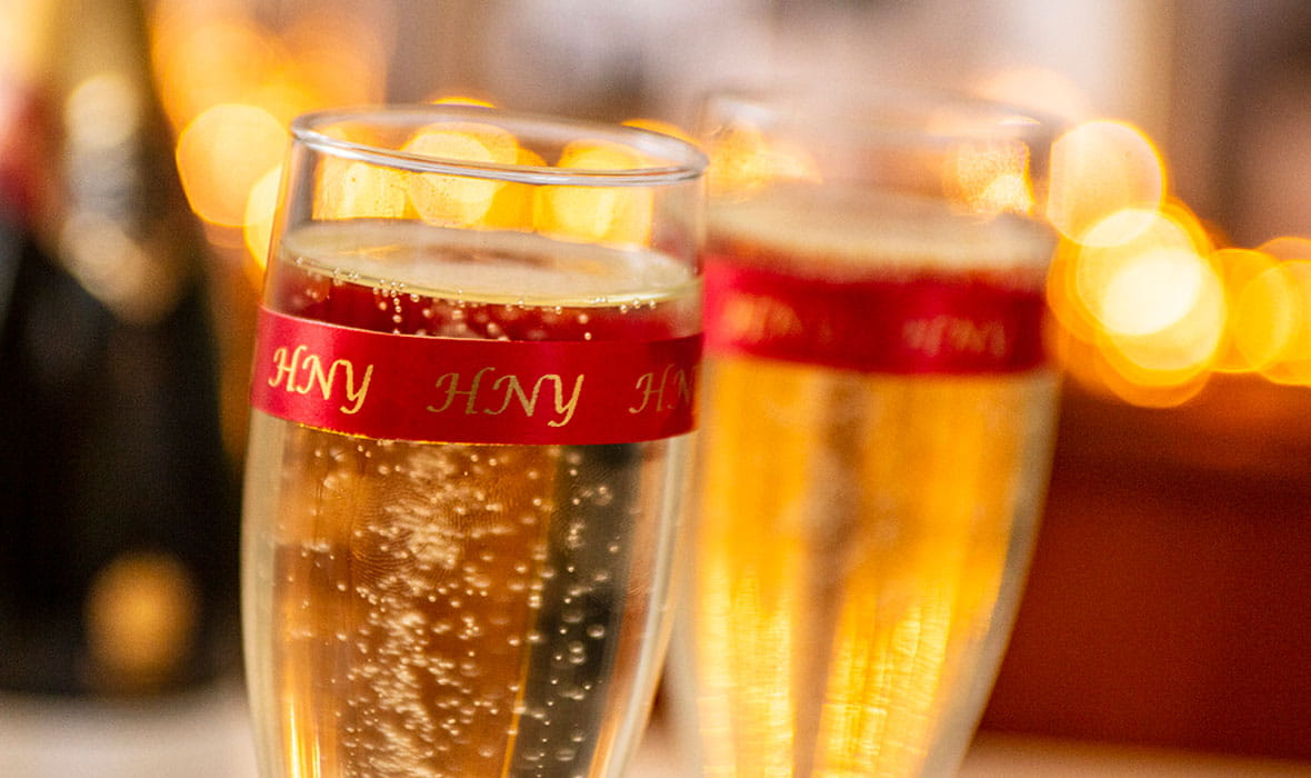 Two champagne flutes wrapped in a Brother satin ribbon with the text
