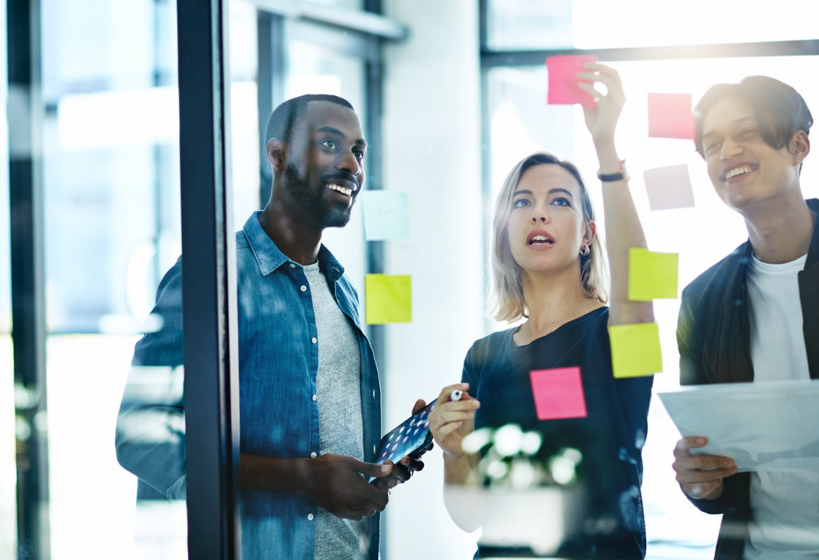 Three office workers stick post-it note stickers onto a glass wall in a moment of creative collaboration during a business meeting