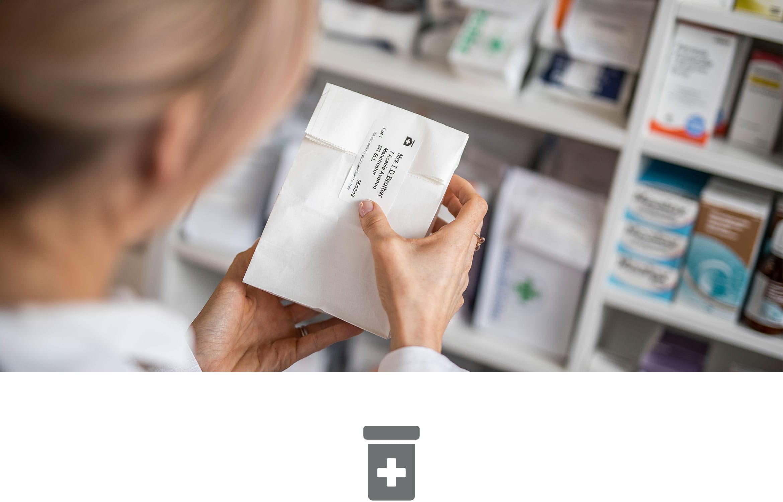 Female pharmacist labelling medication in pharmacy