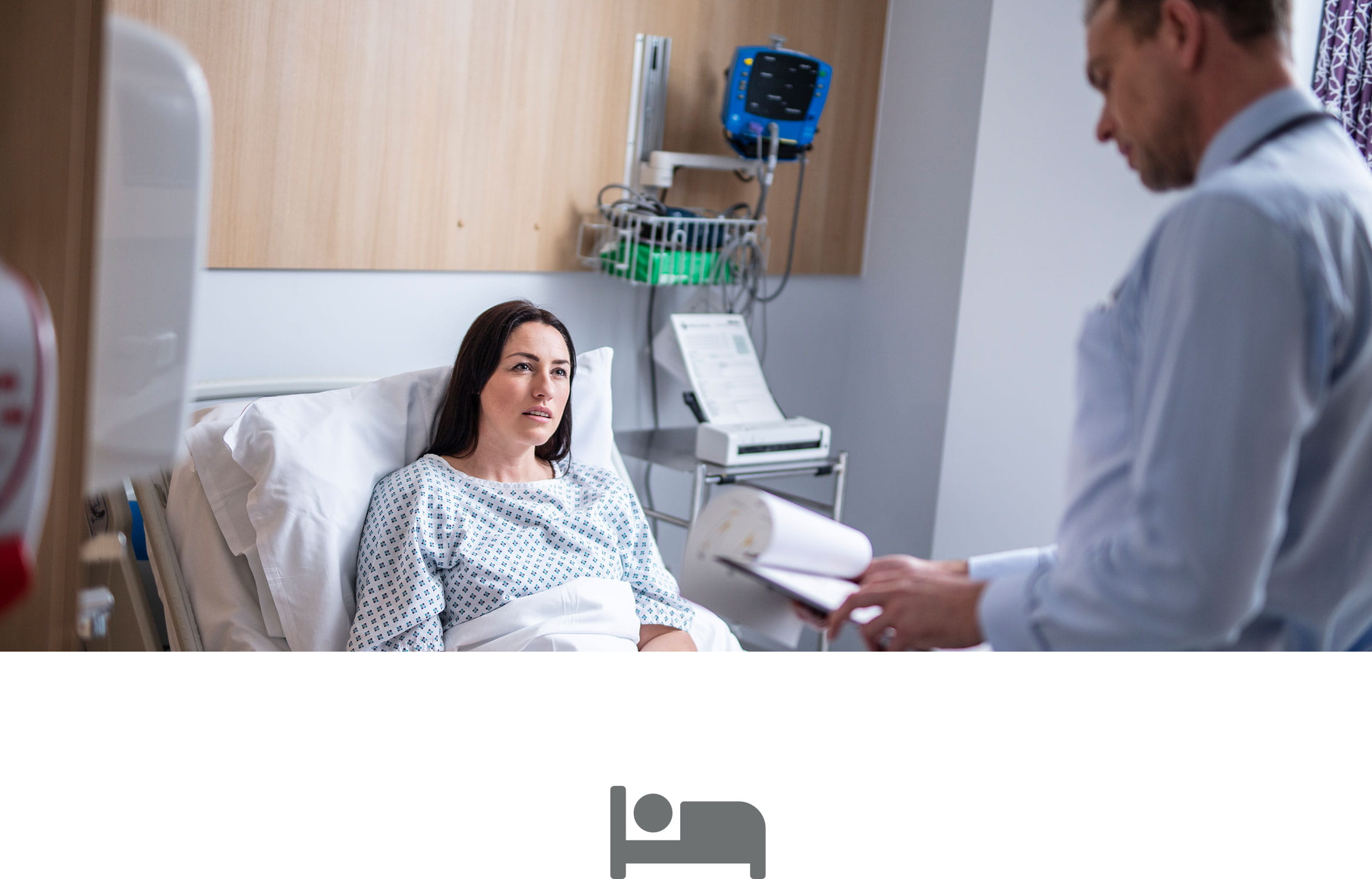 Female patient in hospital bed male doctor looking at patient notes with grey bed icon