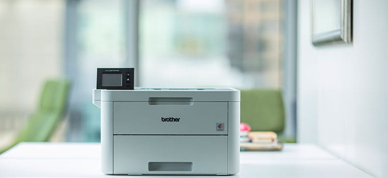 Brother HL-L3270CDW Laser printer on white desk in office green chair in background