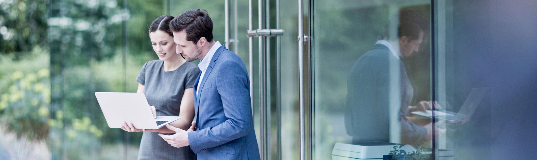 Man with dark hair wearing blue suite white shirt stood speaking to woman wearing grey dress holding laptop outdoors, glass door, printer inside, green bushes