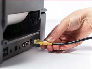 Ethernet cable being plugged into the rear port of a Brother TD-4D label printer