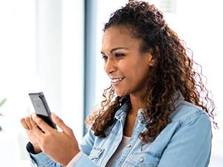 Woman holding smartphone to select the P-touch CUBE Plus label printer from the list of Bluetooth devices