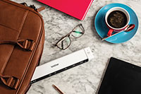 Brother DS-640 portable document scanner, glasses, coffee, leather laptop bag, pencil, tablet, pink notebook