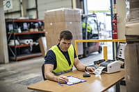 man in warehouse with laptop printing off a distribution label from a continuous roll in a TD4d label printer