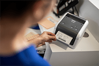Nurse printing patient label using Brother TD-4410D desktop label printer