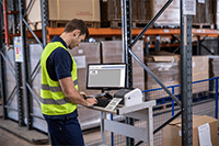 Man wearing hi-vis printing in warehouse using Brother TD-4420DN desktop label printer