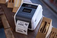 Brother TD-4550DNWB desktop label printer printing food label next to sandwiches
