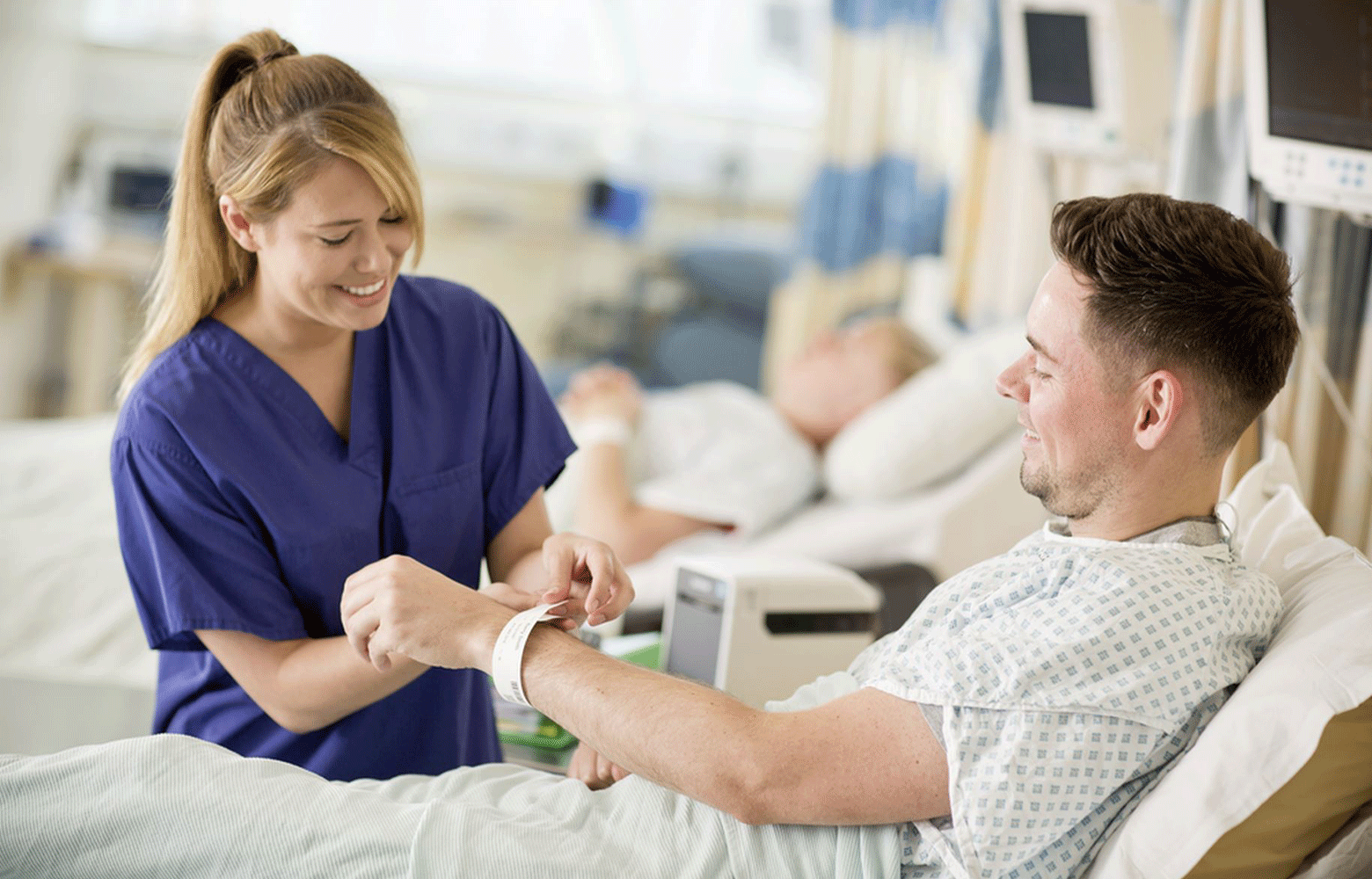 Nurse putting wristband on male patient with TD printer