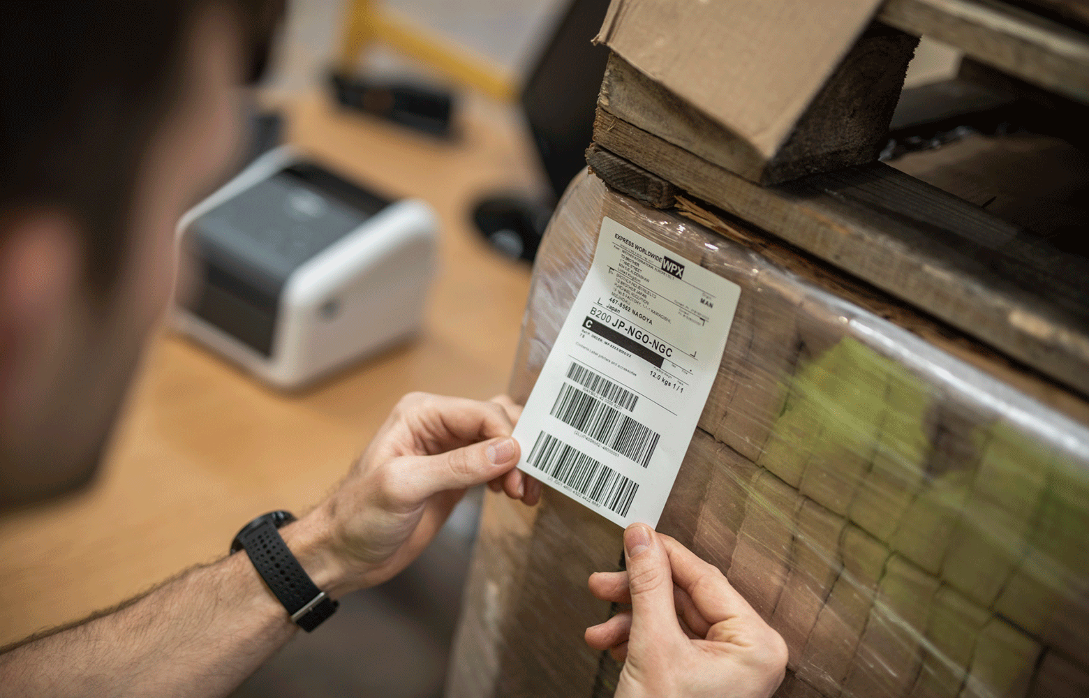 Man labelling boxes with delivery label